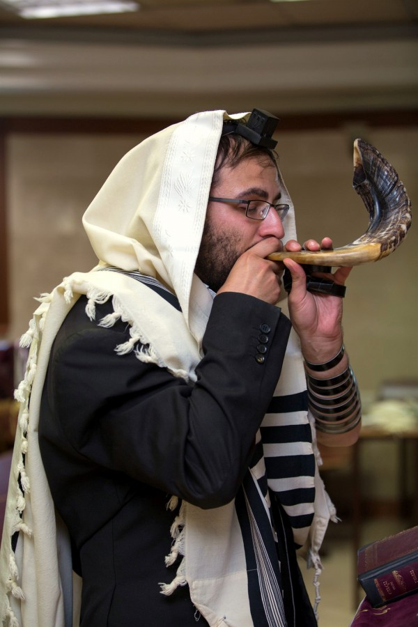 A Jewish man wearing a tallit (prayer shawl) and tefillin (phylacteries) blows a shofar (ram's horn).