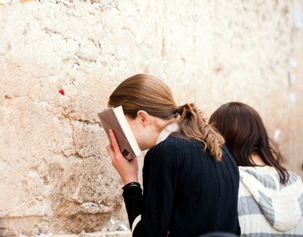 A Jewish young woman buries her face in a siddur (Jewish prayer book) as she prays at the Western (Wailing) Wall.