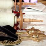 Open Torah scroll with an embroidered Torah mantle (cover) and silver finials for adorning the staves.