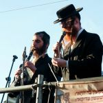 Two ultra-Orthodox Jewish men in Meron, Israel play music during a Jewish holy day.
