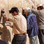 Siddur-Jewish prayer at the Western (Wailing) Wall in Jerusalem. The man wearing tefillin (phylacteries) is reading from a Siddur.