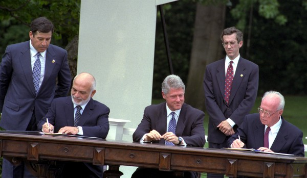 Prime Minister Yitzhak Rabin and Jordan's King Hussein sign the Washington Agreement on the White House lawn as US President Bill Clinton watches.