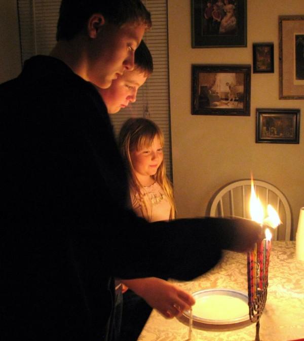 children lighting the hanukkiah