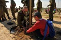 An Israel Defense Forces solder helps a child plant a tree for Tu B'Shvat.