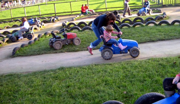 Mother pushes son in go cart