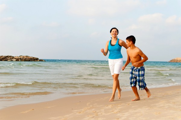 A Jewish mother and son have fun together on a beach in Israel.