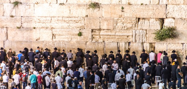 Jewish men pray in the men's section of the Kotel (Western or Wailing Wall)
