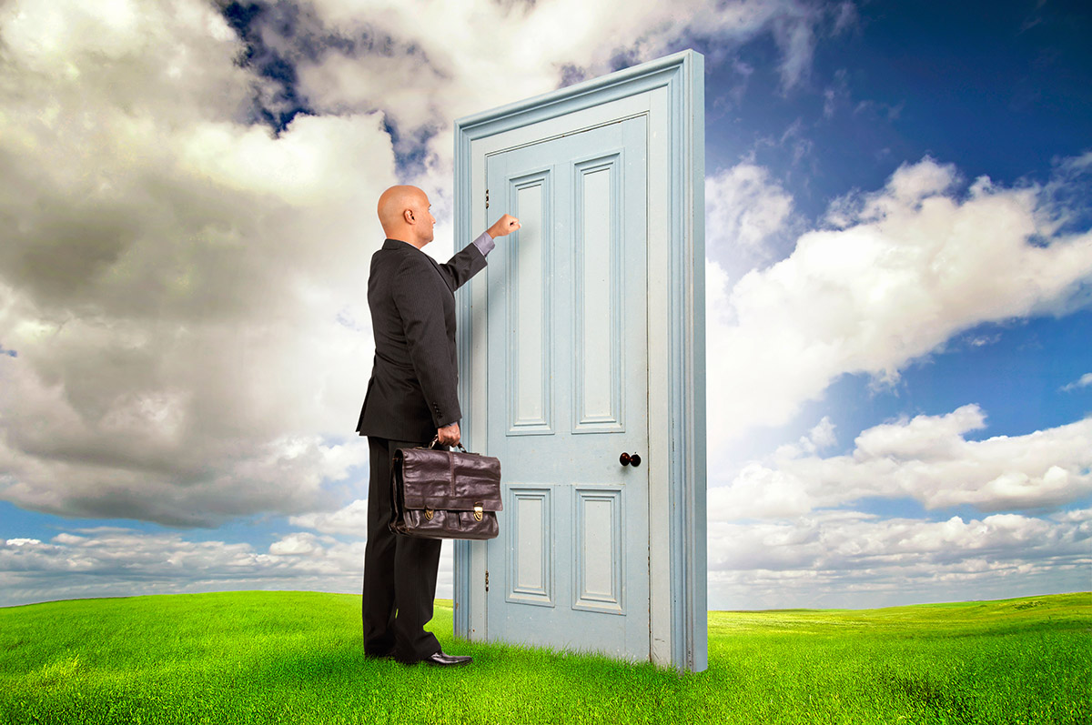 Businessman with briefcase knocking at a door outdoors