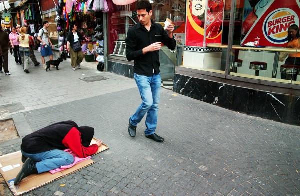 homeless man laying on busy sidewalk of Tel Aviv