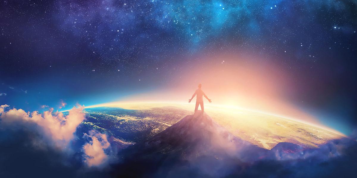 man atop high mountain overlooks earth's horizon