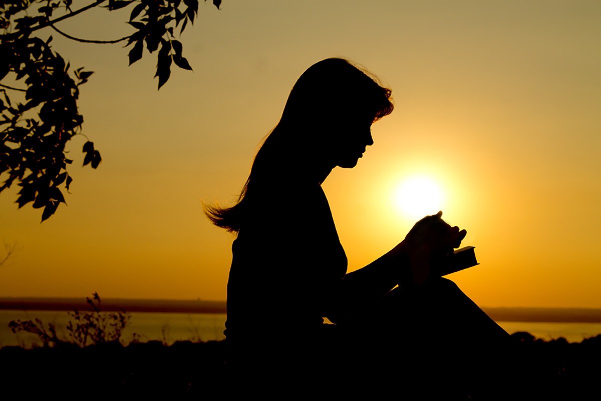 silhouette of young woman praying with open Bible