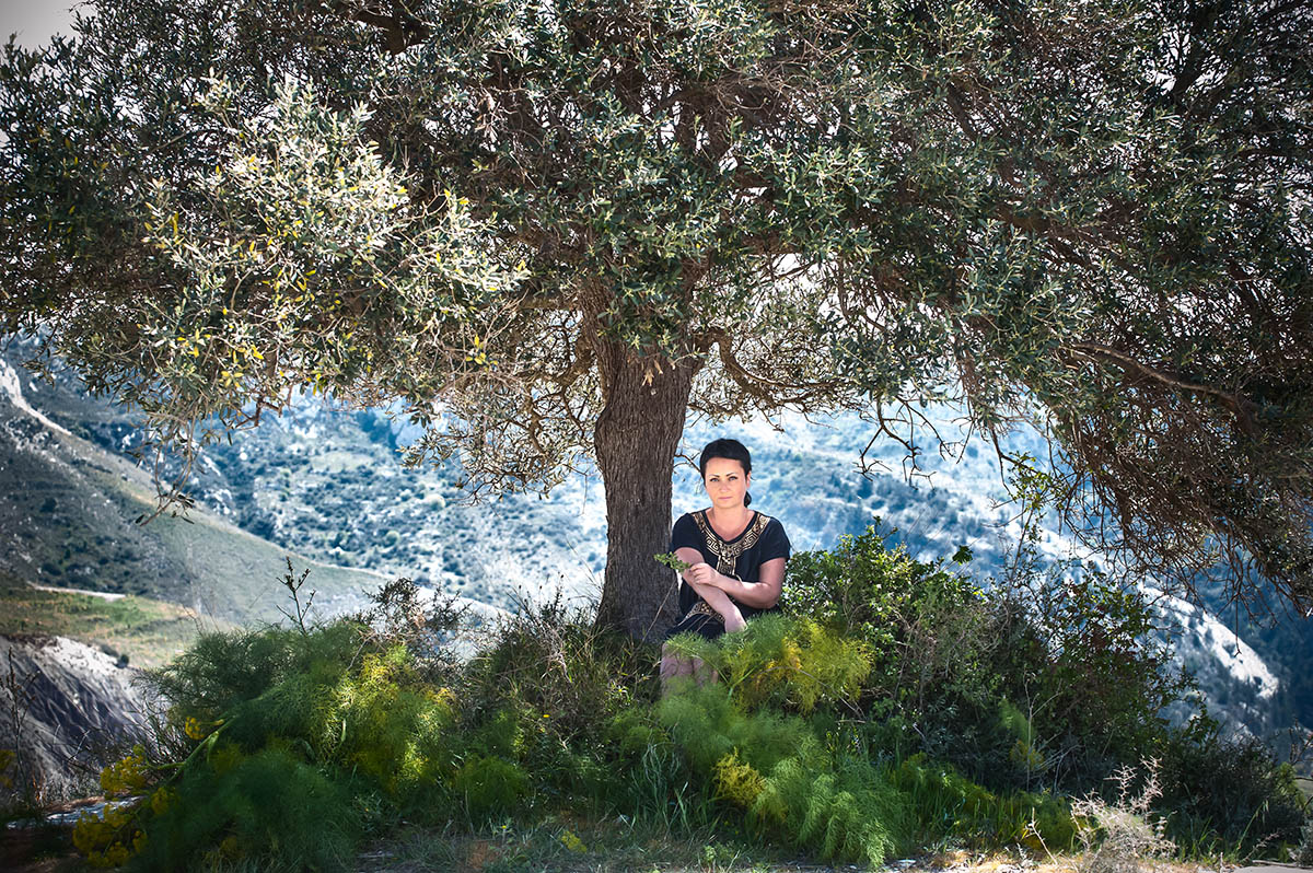Brunette girl under an olive tree on a background of mountains.