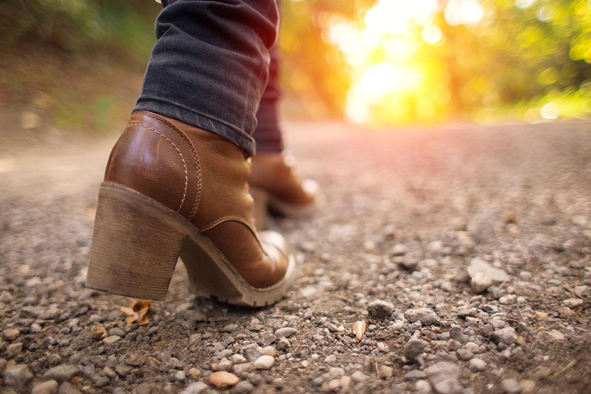 feet walking on path toward sunlight in forest