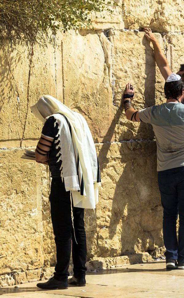 Man wearing a talllit (prayer shawl) is praying at the Western (Wailing) Wall in Jerusalem.