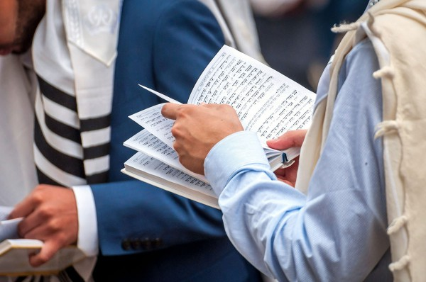 Men wearing tallit (prayer shawls) read from their siddurs (prayer books).