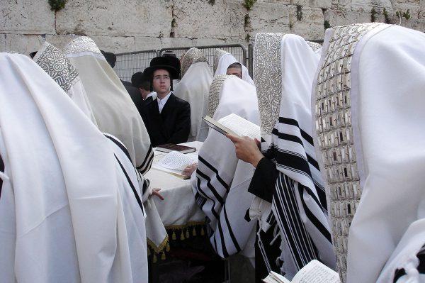 Jewish men wearing their tallit (prayer shawls) pray at the Western(Wailing) Wall in Jerusalem.
