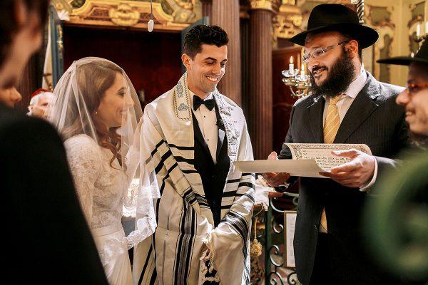 Jewish bride stands next to Jewish groom wearing a tallit (prayer shawl).