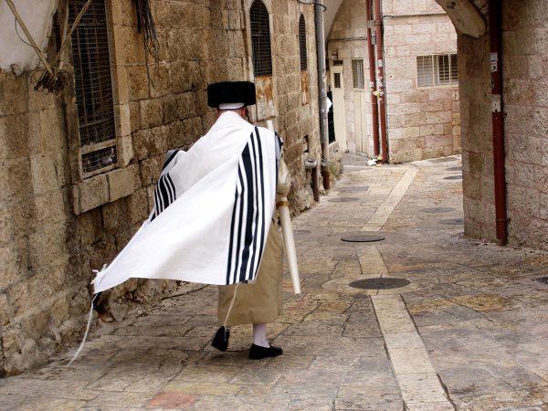 man walks down Jerusalem street wearing a tallit gadol