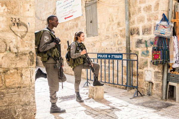 Woman soldier is guiding one of Israel's streets along with her male comrade.