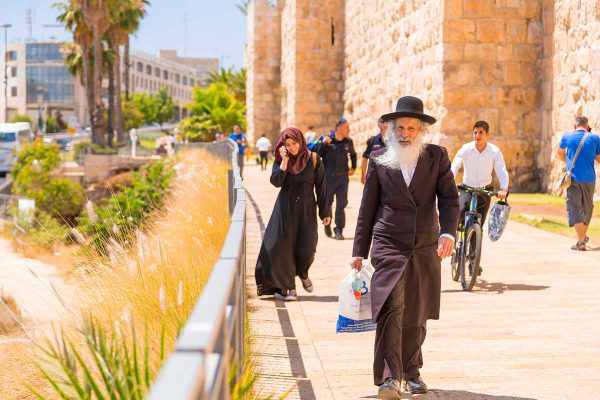 An elderly orthodox Jewish man walks with other Israelis and tourists  outside the Old City walls of Jerusalem.