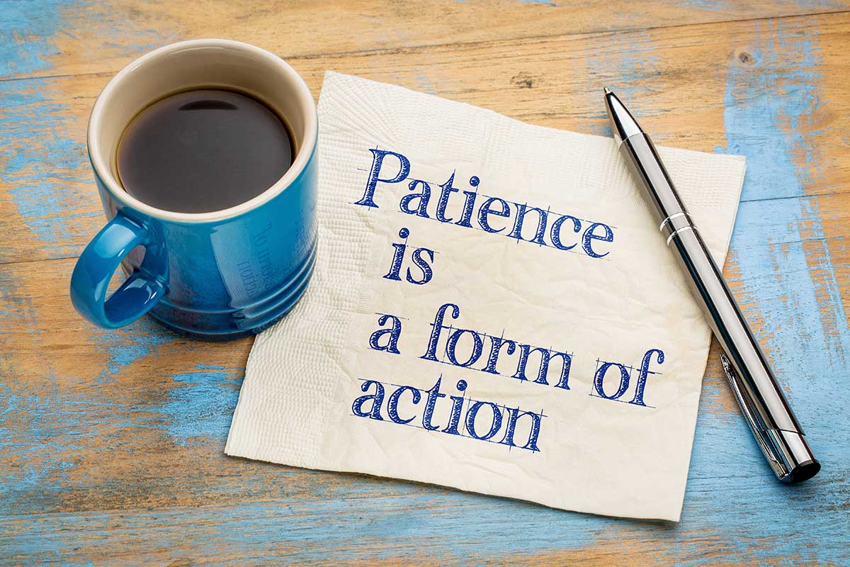 "The words ""patience is a form of action"" are written on a piece of paper with a cup of coffee and a pen on a table."